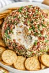 close up of Classic Cheese Ball with a bite taken out and crackers surrounding it on a plate