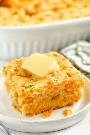 Cornbread Casserole on a white plate with butter and a casserole dish full in the back