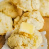 Easy Drop Biscuits on a table with a close up of a biscuit with melted butter on top
