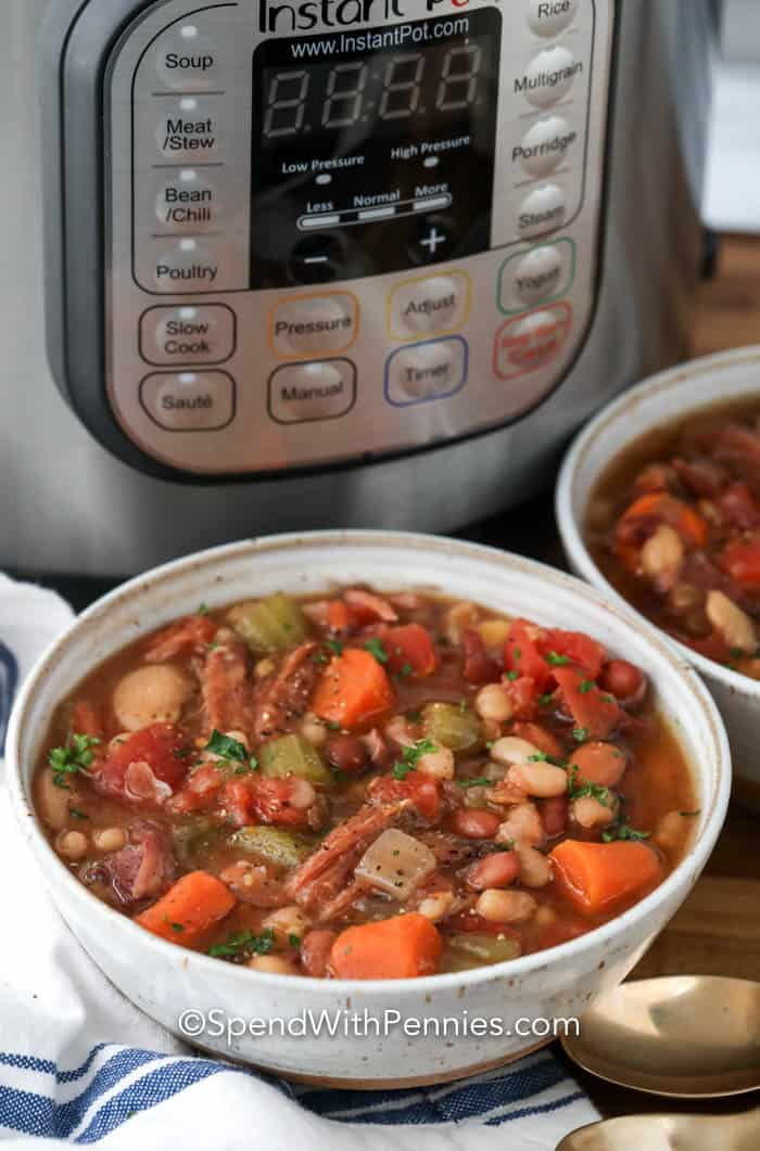 A bowl of ham and bean soup in front of an instant pot