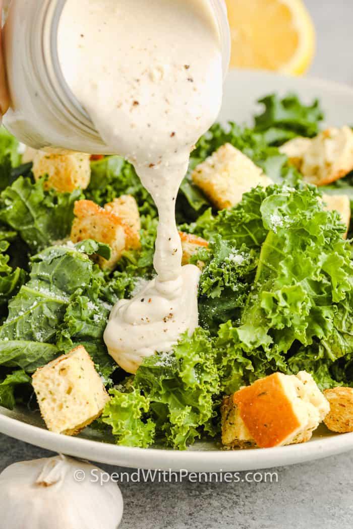 adding dressing to kale to make Kale Caesar Salad