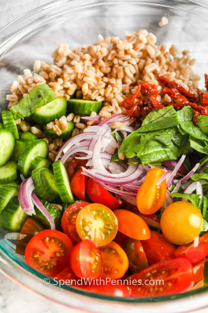 ingredients to make a Mediterranean Farro Salad in a glass bowl