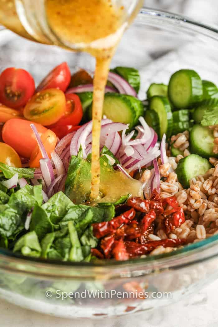 pouring dressing on Mediterranean Farro Salad