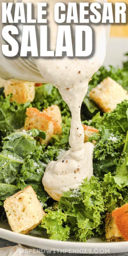 adding dressing to kale to make Kale Caesar Salad with writing