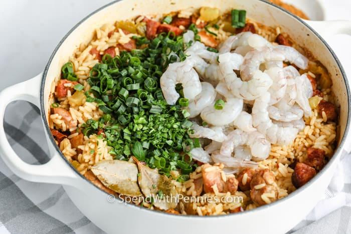 adding shrimp and green onions to Cajun Jambalaya