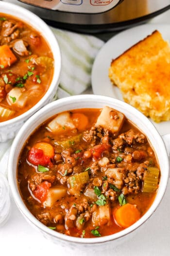 close up of two bowls of Instant Pot Lentil Soup with the instant pot and corn bread in the back