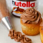 piped Nutella Frosting with cupcakes and nutella jarbeside it