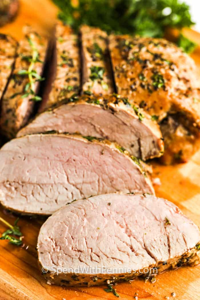 sliced Herb Crusted Pork Tenderloin on a cutting board