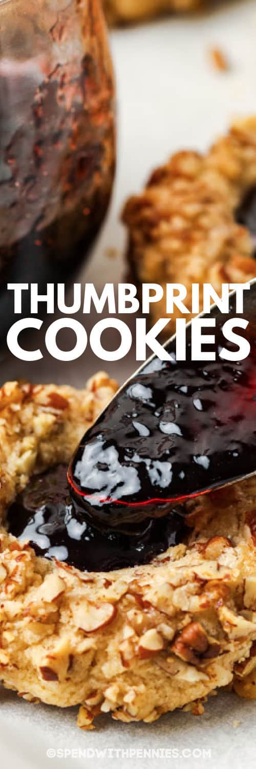filling a cookie with jam to make Classic Thumbprint Cookies with a title
