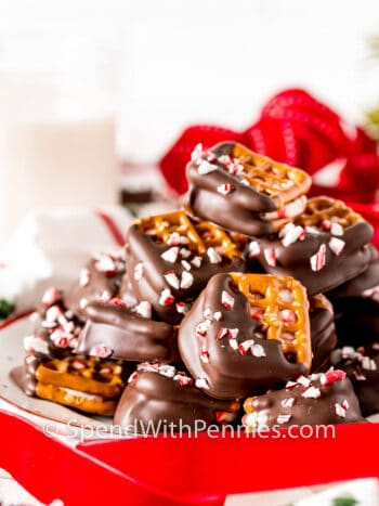 Peppermint Bark Pretzel Bites with ribbon and a glass of milk in the back