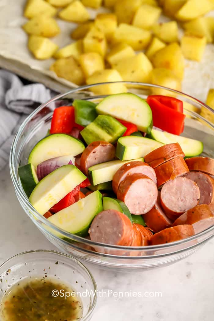 ingredients for Roasted Sausage and Potatoes in a bowls and on a sheet pan