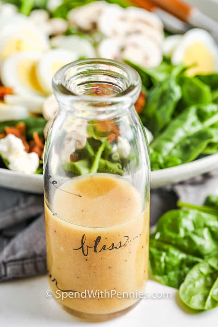 Spinach Salad Dressing in a jar with bowl of salad in the back