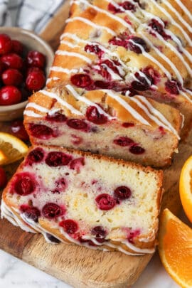 Cranberry Orange Loaf sliced with oranges and cranberries surrounding it