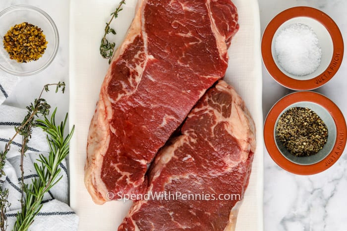 steak on a plate with seasonings in bowls to show How to Cook Juicy Steaks in the Oven