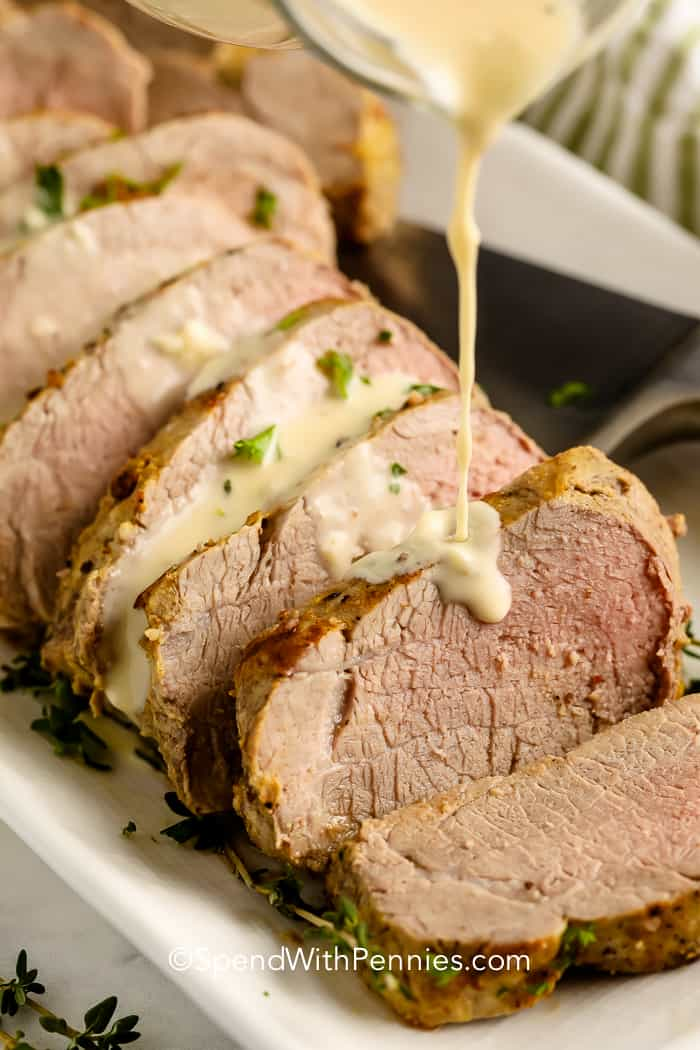 Pork Tenderloin with Dijon Sauce being poured on