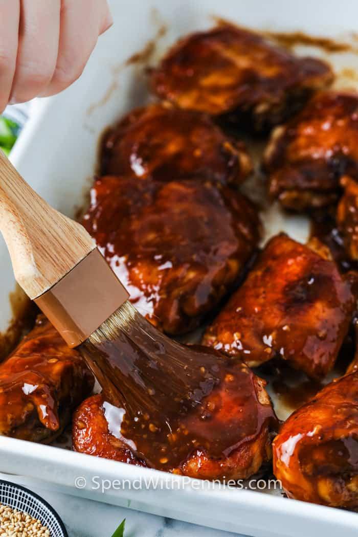 brushing sauce on chicken to make Baked Teriyaki Chicken