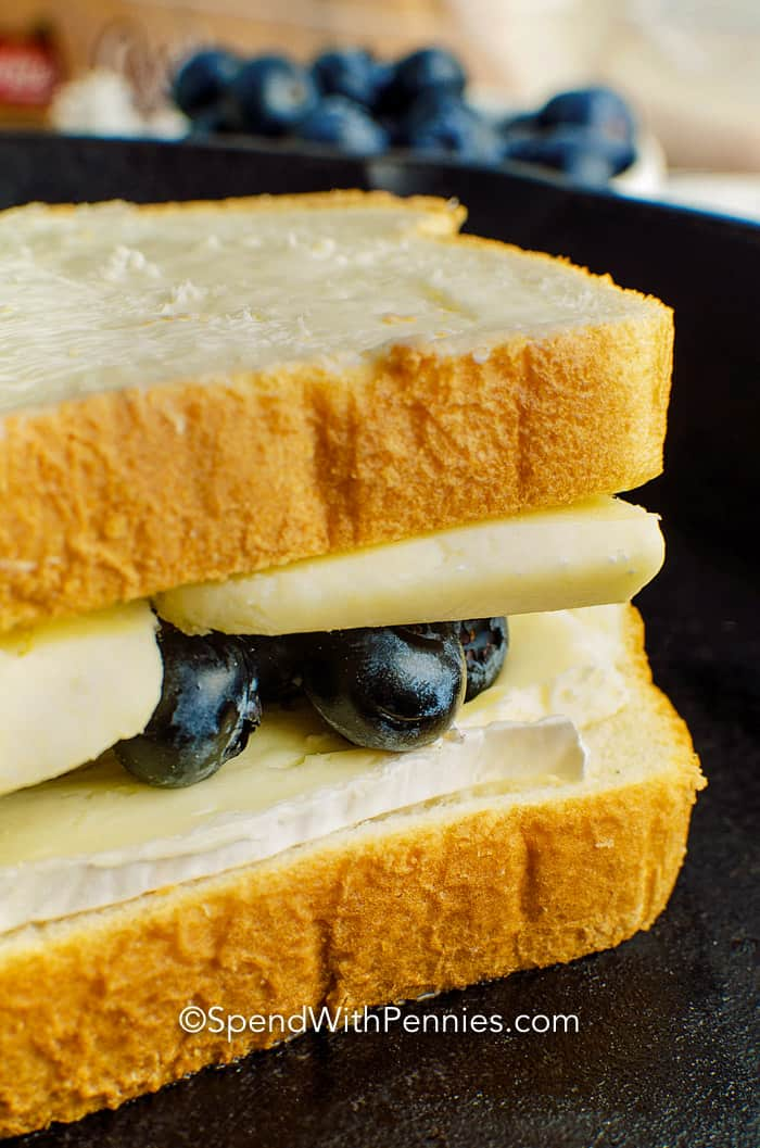 An uncooked blueberry brie grilled cheese sandwich prepared