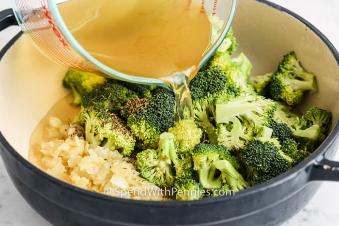pouring broth into pan to make Broccoli Cheddar Soup