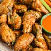 Actually Crispy Oven Baked Wings on a baking sheet with celery and carrots and writing