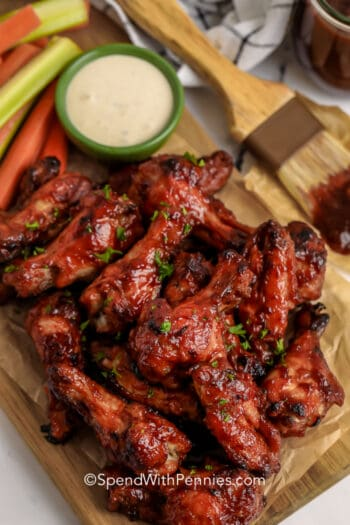 BBQ wings on a wooden board with dip