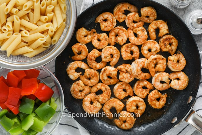 cooked shrimp in the pot and ingredients in bowls to make Cajun Shrimp Pasta