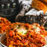 close up of Crockpot Lasagna with bread and a slow cooker in the back