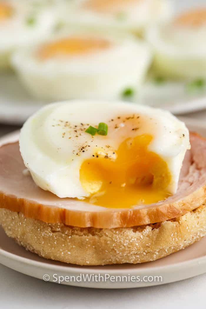 egg and ham on an english muffin with Oven Poached Eggs on a plate in the back