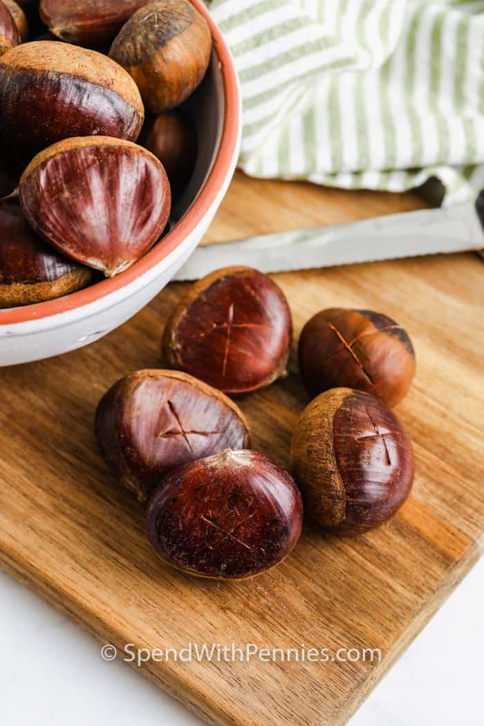 marking an x on the chestnuts with a knife to make Roasted Chestnuts