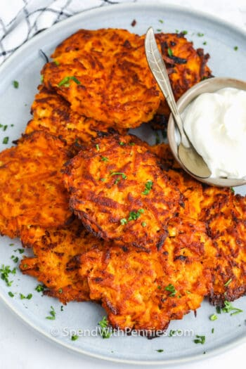 Sweet Potato Hash Browns on a plate with a bowl of sour cream beside it