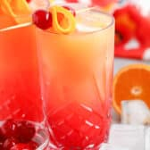 two glasses of Tequila Sunrise with cherries , oranges and ice cubes