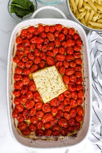 baked feta and tomatoes in a casserole dish with pasta