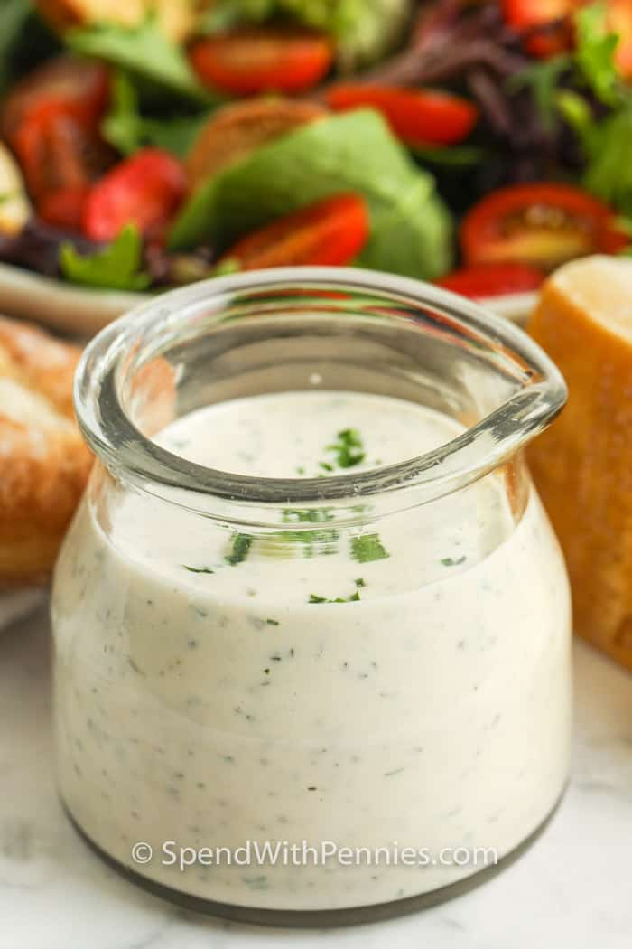 jar of Creamy Italian Dressing with salad in the back