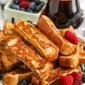 French Toast Sticks with syrup and berries in the back