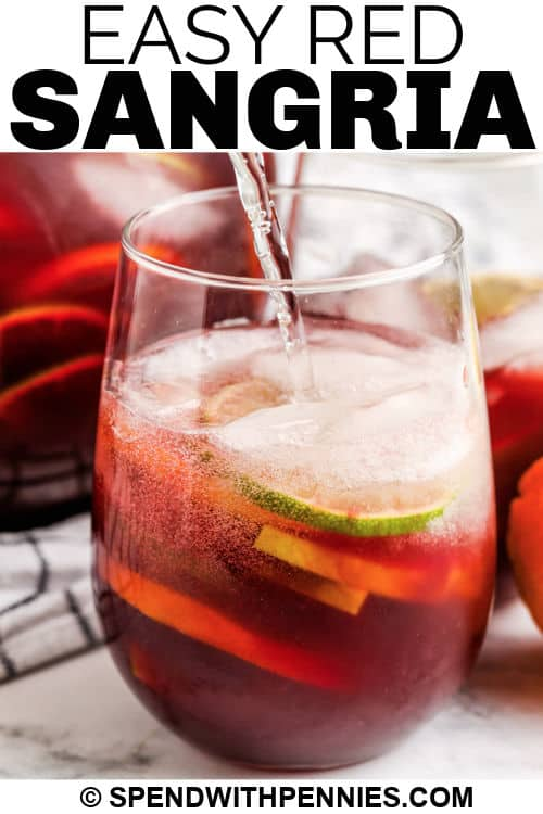 adding club soda to glass of Red Sangria with a title