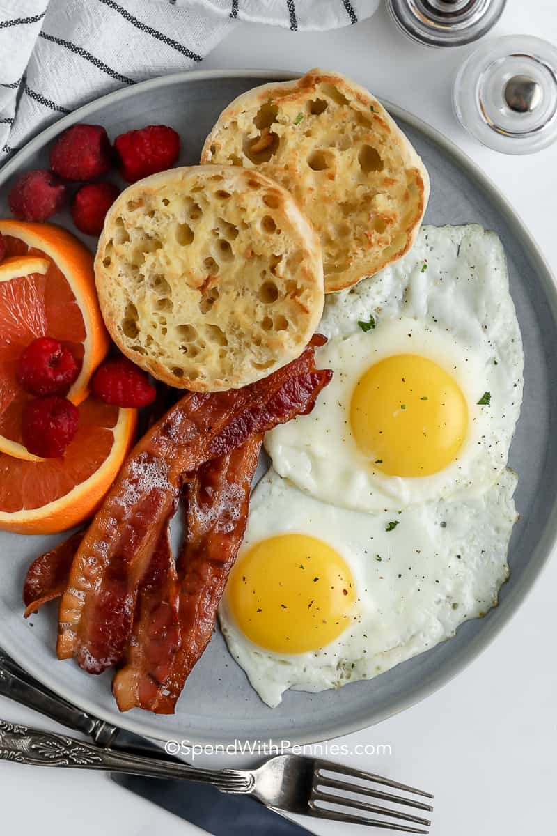 fried eggs on plate with english muffin, bacon, and fruit