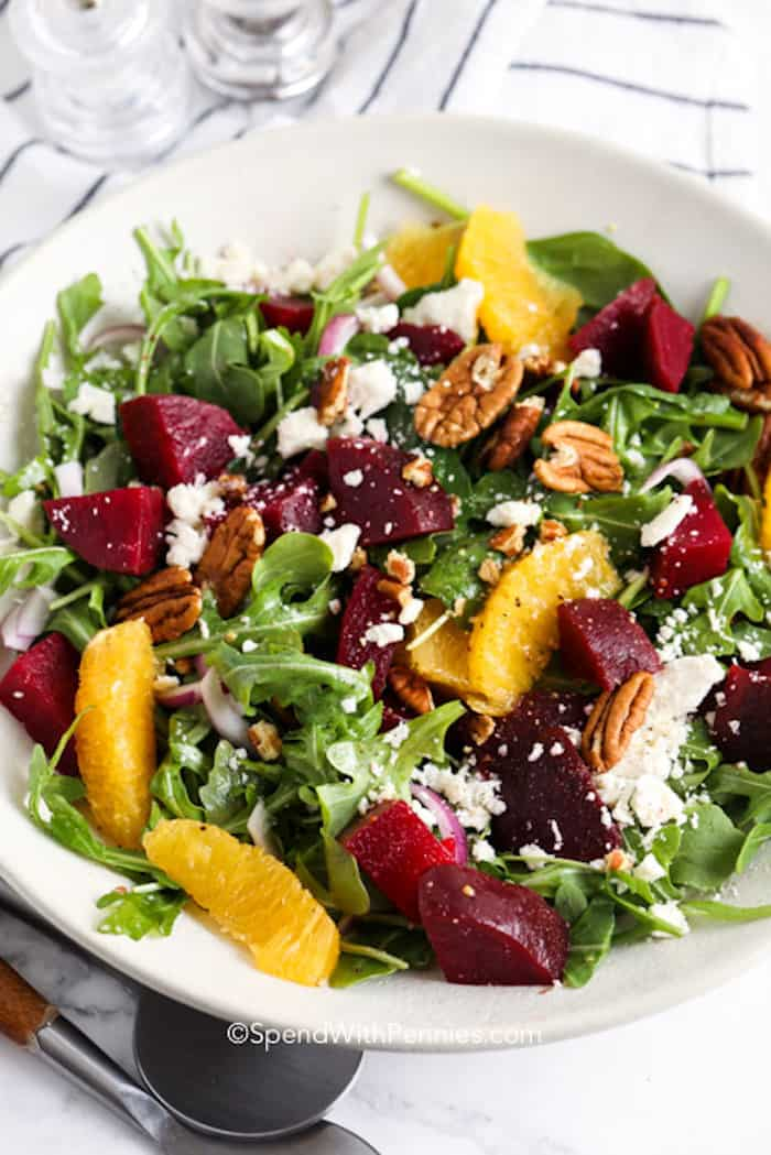 Arugula salad topped with beets and oranges