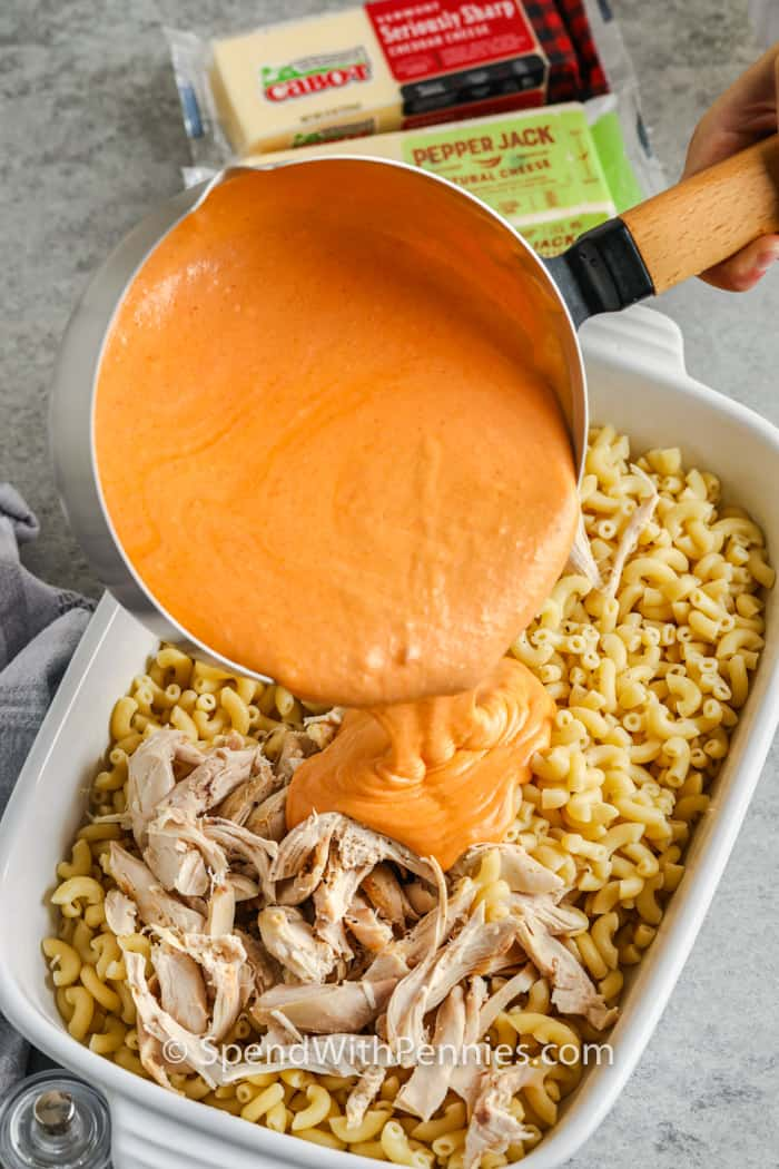 pouring sauce on chicken and noodles to make Buffalo Chicken Mac and Cheese