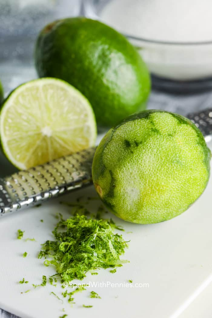 a zested lime on a cutting board with a microplane grater
