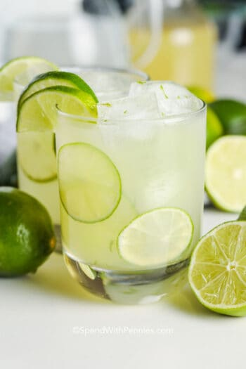 A glass of limeaid with ice and lime slices