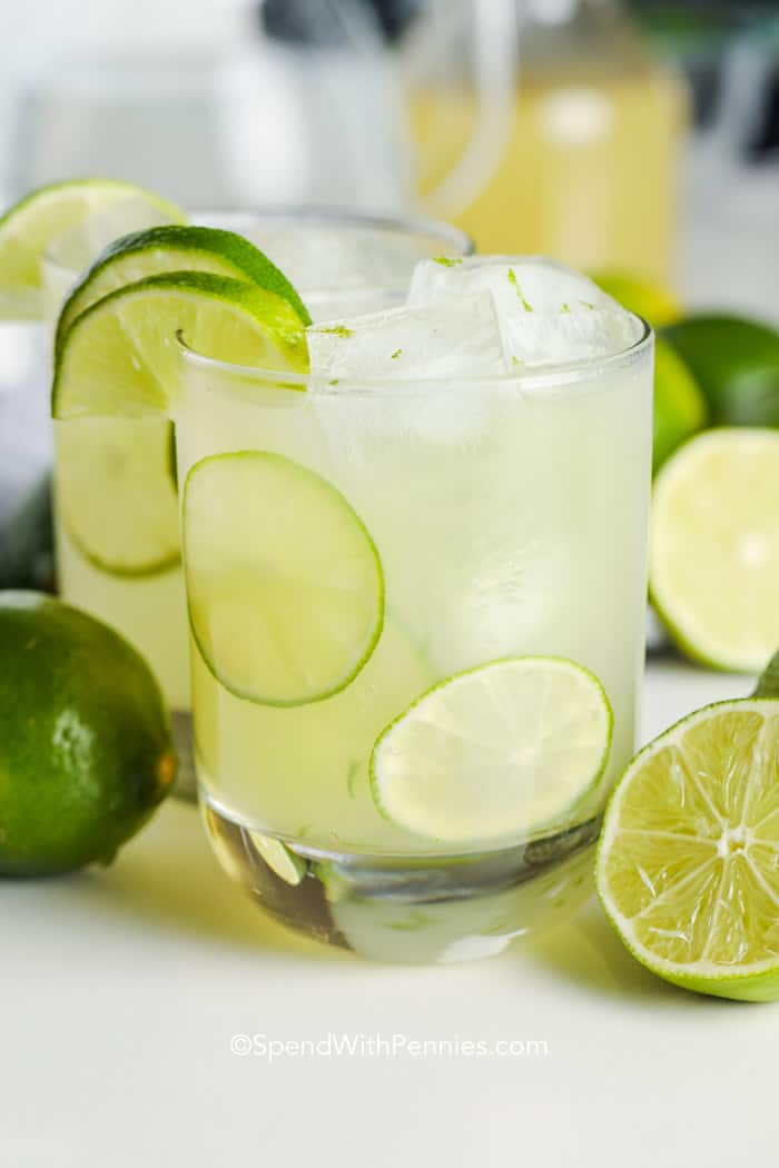 A glass of limeade with ice and lime slices