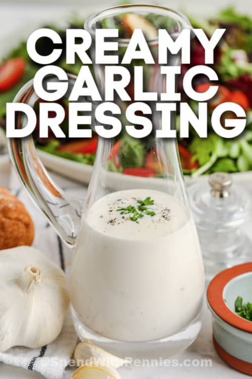 Creamy Garlic Dressing in a glass with salad in the back