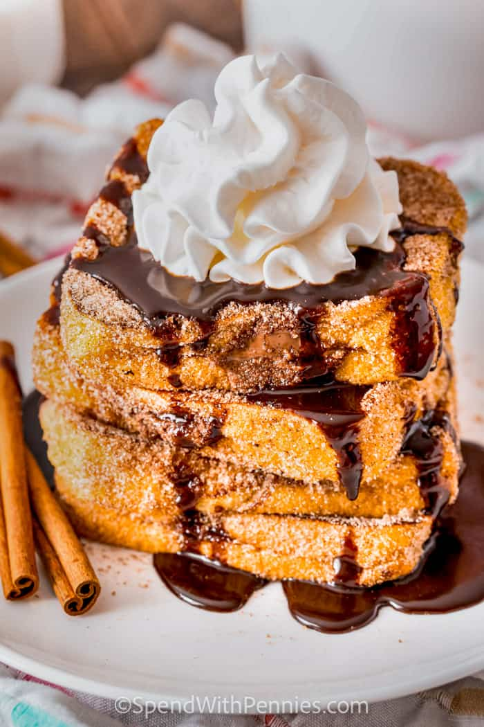 Nutella Stuffed Churro French Toast with whipping cream and chocolate sauce