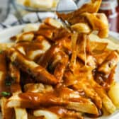 fork full of Poutine with plate full behind it