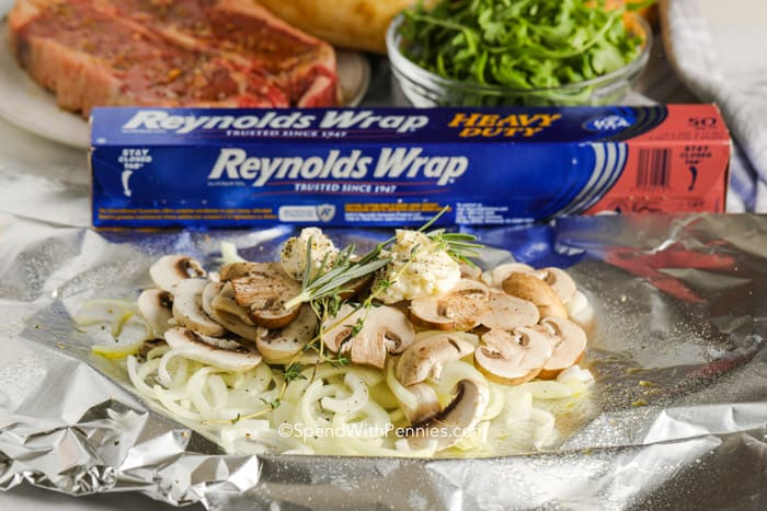 Onions and mushrooms with herbs on tinfoil