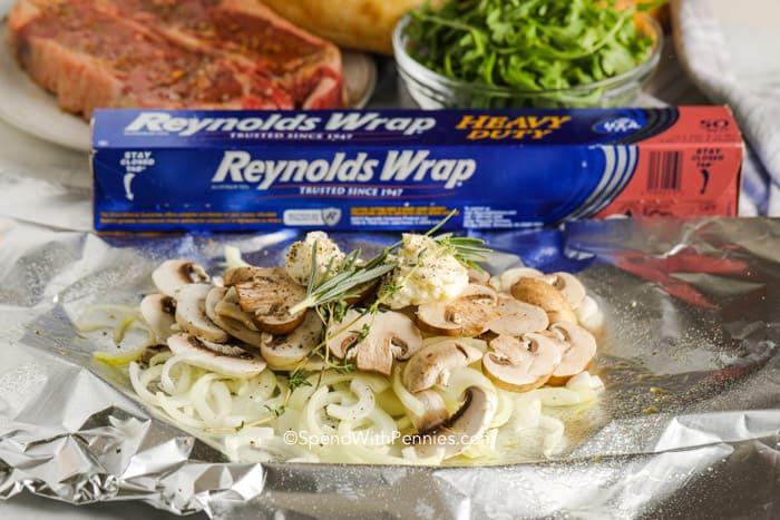 Mushroom, onions, and herbs on foil.