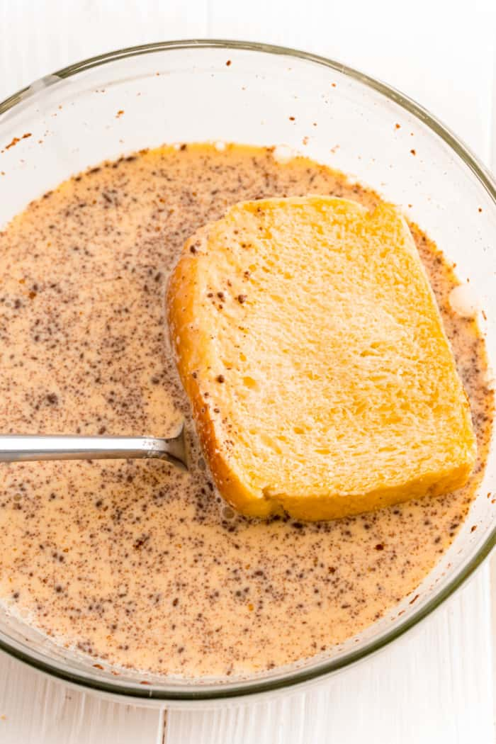 dipping bread in an egg mixture for French toast