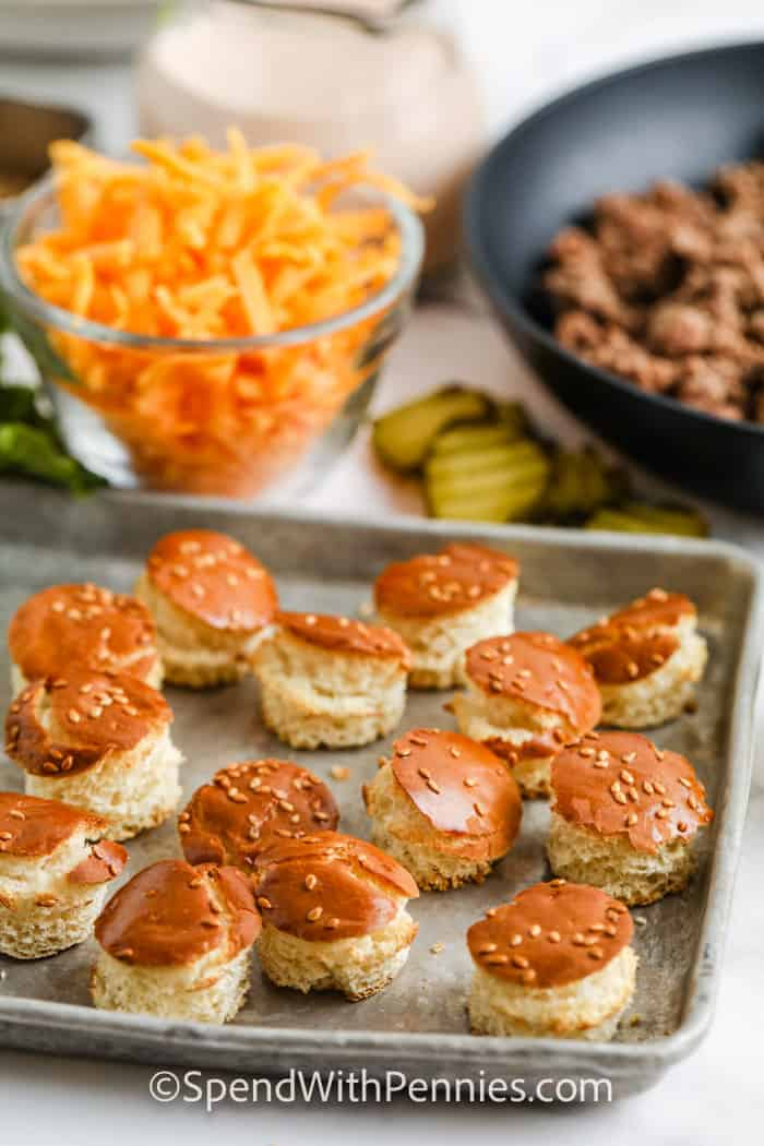 cut out cheeseburger buns toasted on a baking sheet with ingredients to make Big Mac Salad