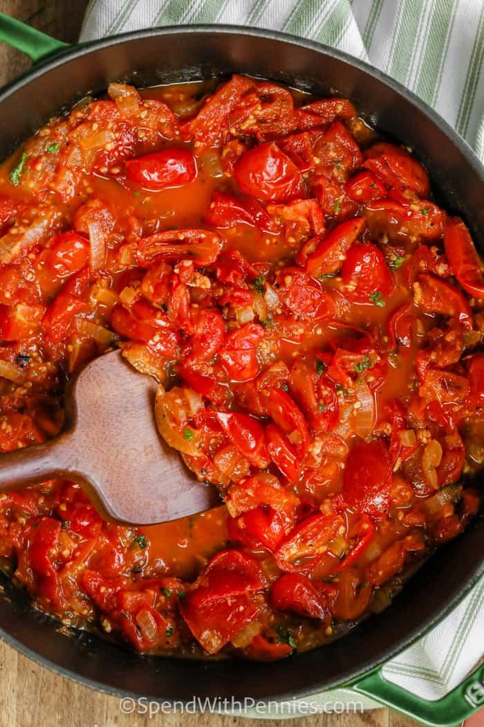 stirring sauce to make Bucatini with Fresh Tomato Sauce