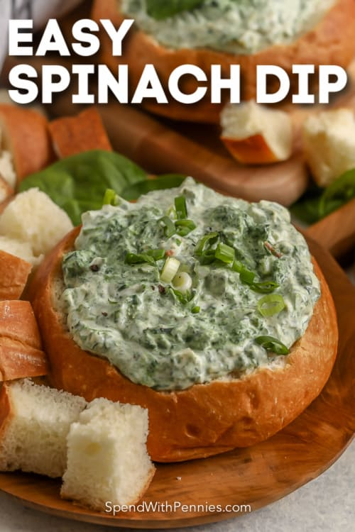 spinach dip in a bread bowls on a wood plate with text
