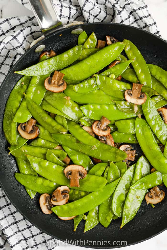 cooking Snow Peas and Mushrooms in the pan